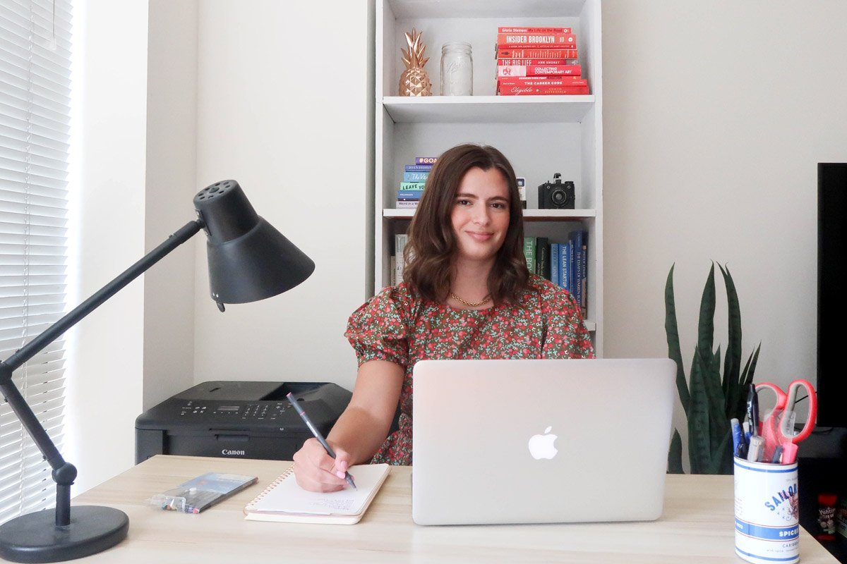 A woman sits at her home desk.